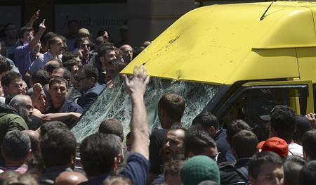 A crowd attacks a minibus carrying gay rights activists during an International Day Against Homophobia and Transphobia (IDAHO) rally in Tbilisi